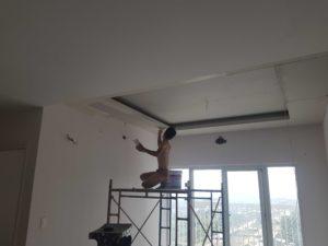 Người thợ sơn lại chung cư đang trét bột cho trần